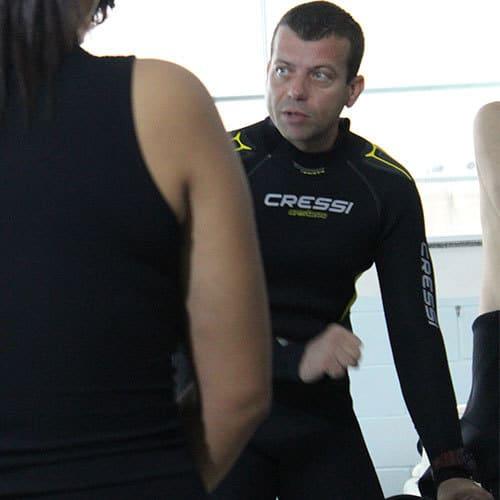 Instrutor ensinando a mergulhar em piscina